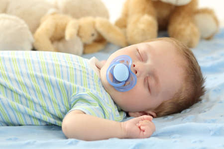 Foto de Cute baby sleeping with a pacifier on a bed - Imagen libre de derechos