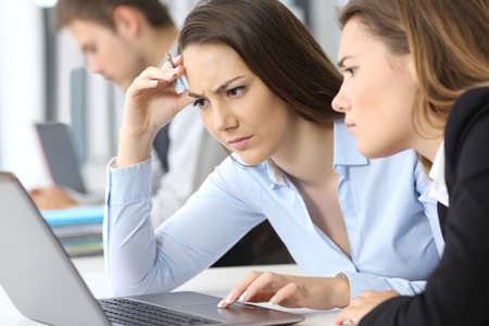 Photo pour Two worried businesswomen working on line with a laptop at office - image libre de droit