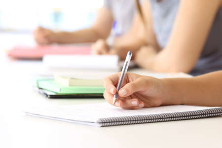 Photo pour Close up of a student hand taking notes in a notebook at classroom - image libre de droit