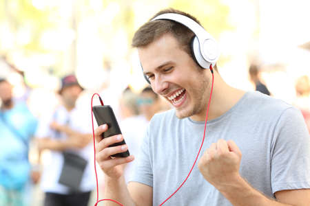 Photo pour Excited guy receiving good news on a mobile phone on the street - image libre de droit