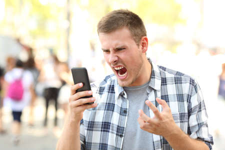 Photo pour Angry man holding crashed mobile phone on the street - image libre de droit