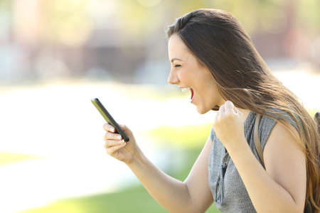 Foto de Profile of a single excited woman using a smart phone outdoors in the street - Imagen libre de derechos
