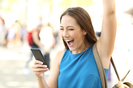Foto de Excited woman raising arm receiving good news on a mobile phone on the street - Imagen libre de derechos