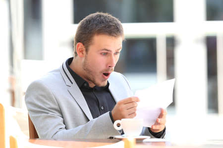 Photo for Portrait of an amazed executive reading a letter sitting in a coffee shop - Royalty Free Image