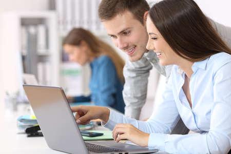 Foto de Two happy colleagues coworking on line together with a laptop at office - Imagen libre de derechos