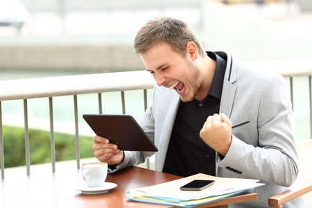 Foto de Excited executive receiving good news on line sitting in a coffee shop - Imagen libre de derechos