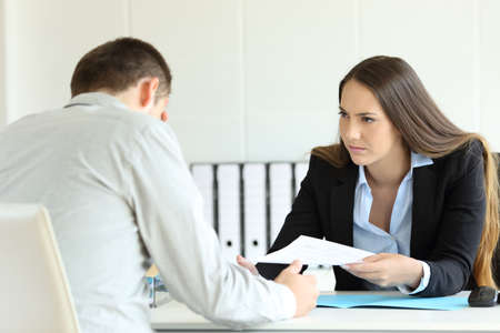 Photo for Angry boss giving a document to a sad employee sitting in a desk at office - Royalty Free Image