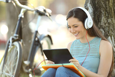 Foto de Happy student watching media content on line in a tablet sitting in a park - Imagen libre de derechos