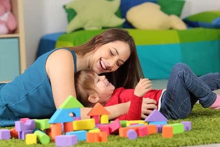 Foto de Mother or nanny playing with a child on the carpet in a room at home - Imagen libre de derechos