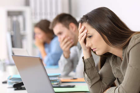 Photo for Portrait of three worried employees reading bad news on line at office - Royalty Free Image