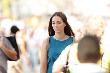 Foto de Sad woman feeling alone walking between people on the street - Imagen libre de derechos