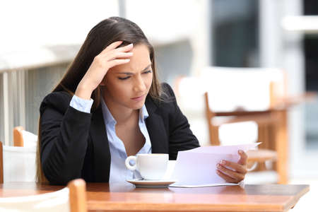 Photo for Worried executive reading a letter sitting in a coffee shop - Royalty Free Image