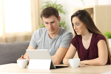Photo for Confused couple receiving on line news sitting in a desk at home - Royalty Free Image