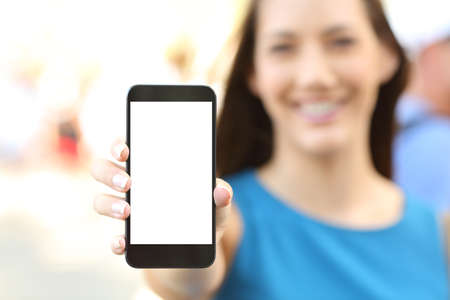 Foto de Close up of a female showing a blank vertical phone screen on the street - Imagen libre de derechos