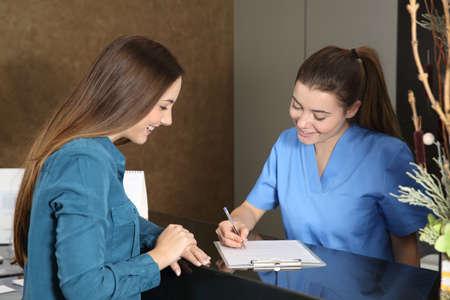 Photo pour Nurse or dentist attending a client in a clinic reception - image libre de droit