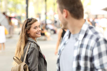 Photo for Strangers girl and guy flirting looking each other on the street - Royalty Free Image