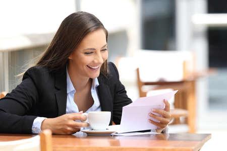 Photo pour Single happy businesswoman reading a letter sitting in a coffee shop - image libre de droit