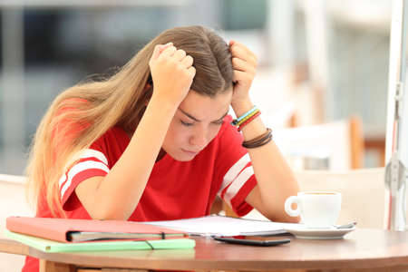Foto de Single frustrated student girl trying to understand notes sitting in a bar - Imagen libre de derechos
