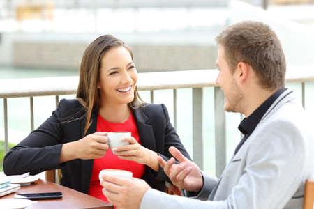 Foto de Two happy executives talking during a coffee break sitting in a bar - Imagen libre de derechos