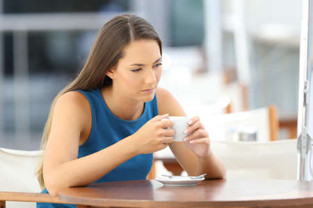 Photo for single longing pensive woman sitting in a coffee shop - Royalty Free Image