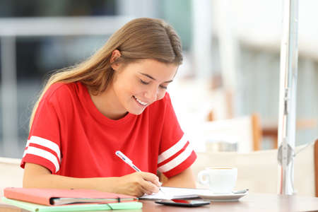 Photo for Happy student girl studying taking notes sitting in a coffee shop - Royalty Free Image