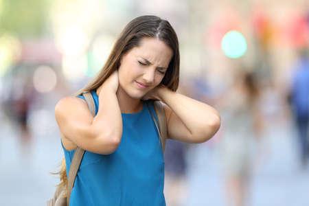 Photo pour Single woman suffering neck ache walking on the street - image libre de droit