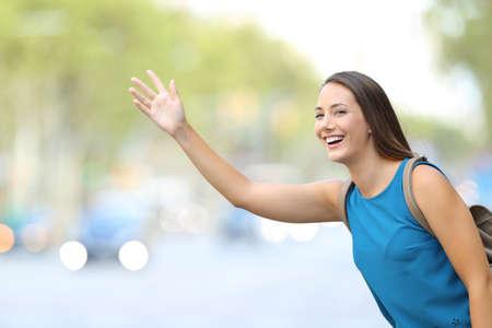 Photo pour Single happy woman hailing taxi cab on the street - image libre de droit