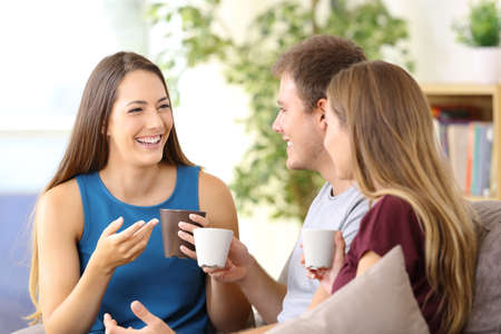 Photo pour Three happy friends talking and drinking coffee sitting on a couch at home - image libre de droit