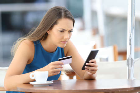 Photo pour Single worried girl having problems paying on line with a credit card and a phone in a coffee shop terrace - image libre de droit