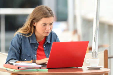 Photo for Single confused student searching on line with a red laptop sitting in a bar terrace - Royalty Free Image
