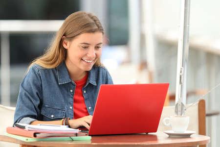 Foto de Single happy student typing on a laptop sitting in a bar terrace - Imagen libre de derechos
