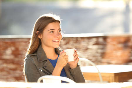 Photo pour Single happy teen resting and looking away holding a cup sitting in a coffee shop with a warm light in the background - image libre de droit