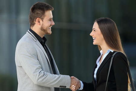 Photo for Side view of two happy executives meeting and handshaking on the street with an office building in the background - Royalty Free Image