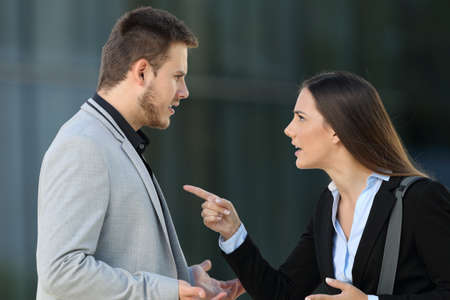 Foto de Side view of an angry couple of executives arguing standing on the street - Imagen libre de derechos