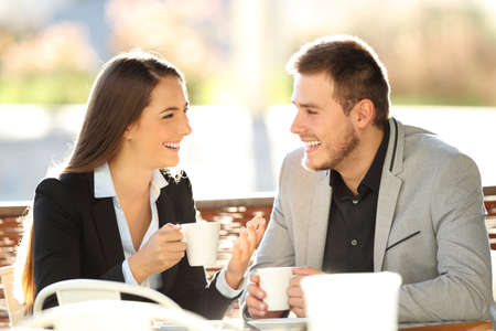 Photo for Two executives talking during a cofee break sitting in a bar terrace with a warm backlight - Royalty Free Image