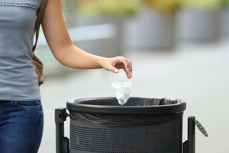 Foto de Close up of a civic woman hand throwing garbage in a trash bin on the street - Imagen libre de derechos