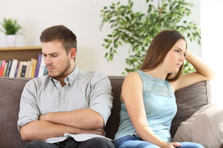 Foto de Angry couple ignoring each other after argument sitting on a sofa at home - Imagen libre de derechos