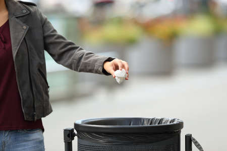 Photo for Close up of a lady hand throwing garbage to a trash bin on the street - Royalty Free Image