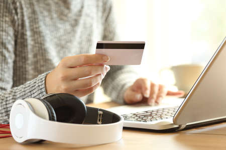Photo pour Close up of an on line buyer hands buying music with a laptop and credit card at home - image libre de droit