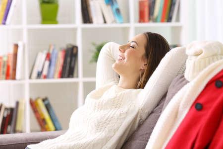 Foto de Side view of a woman relaxing sitting on a sofa when she gets home in winter - Imagen libre de derechos