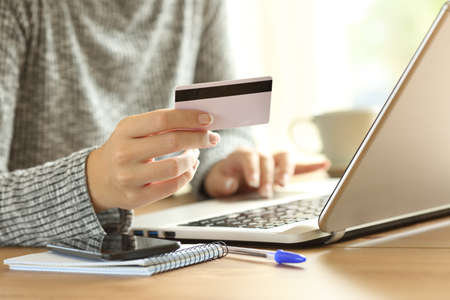 Photo pour Close up of a woman hand paying on line with credit card and a laptop on a desktop at home - image libre de droit