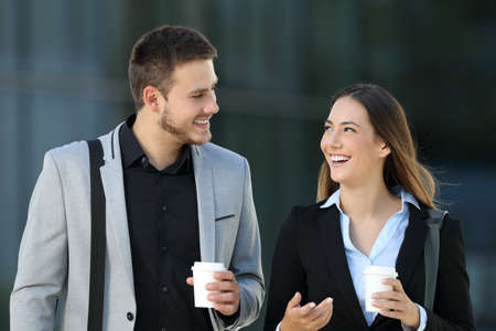 Photo for Happy couple of executives walking towards camera and conversing on the street with an office building in the background - Royalty Free Image