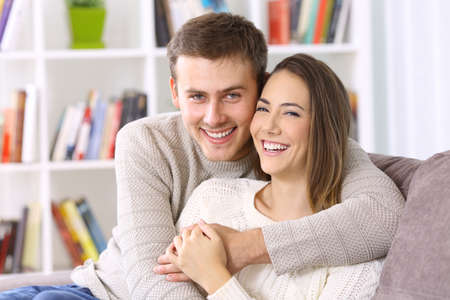 Photo pour Portrait of a happy couple posing together wearing sweaters looking at camera on a couch at home in winter - image libre de droit
