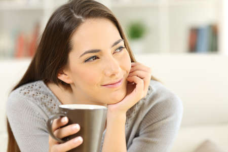 Photo pour Pensive woman holding a coffee cup looking at side sitting on a sofa in the living room at home - image libre de droit