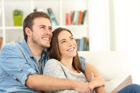 Photo pour Happy couple dreaming looking above sitting on a sofa in the living room at home - image libre de droit