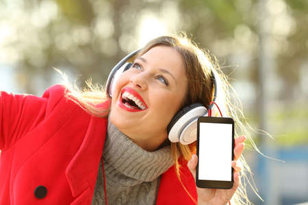 Photo for Happy girl wearing red jacket and headphones listening to music and showing smartphone screen in a park in winter - Royalty Free Image