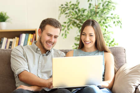 Foto de Front view portrait of a young happy couple using a laptop together sitting on a sofa in the living room at home - Imagen libre de derechos