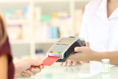 Photo pour Close up of a pharmacist hands charging with credit card reader on a counter in a pharmacy - image libre de droit