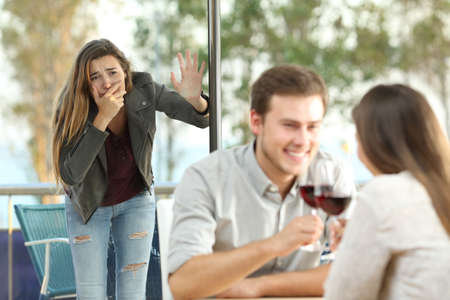 Photo pour Cheater caught by his sad girlfriend dating with another girl in a coffee shop - image libre de droit