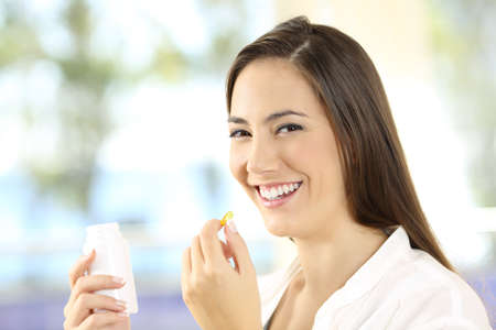 Photo pour Portrait of a happy woman holding a vitamins pill and bottle - image libre de droit